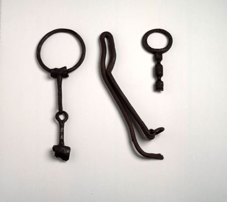 Postcard of Iron bridle bit, an iron latch lifter and a bronze mirror handle.