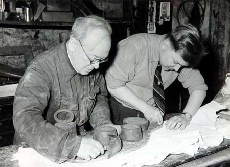 Postcard of Andrew Ross, Sr. and Andrew Ross, Jr. cutting sheepskin for pipe bags.
